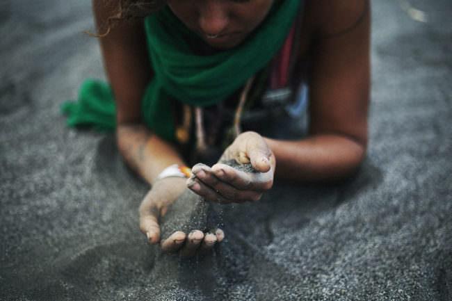 Eine Frau mit dunkelm Sand zwischen den Händen