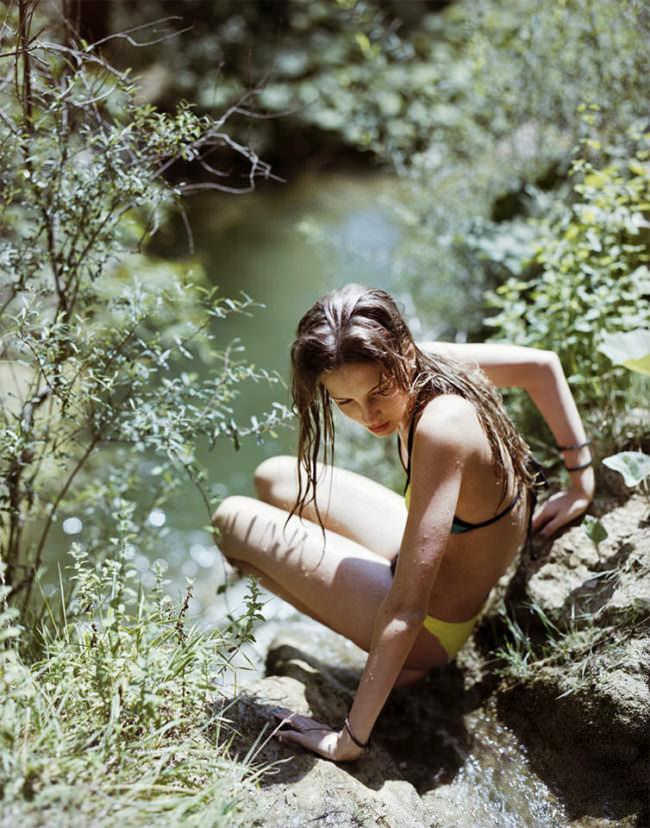 Junges Mädchen im Bikini kniet an einem See im Gebüsch.