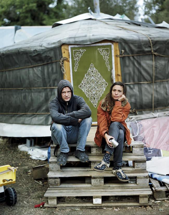 Zwei junge Personen warm angezogen vor etwas, das wie ein Zelt anmutet, auf Paletten sitzend.