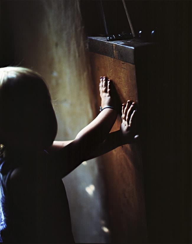 Silhouette eines Kleinkindes, das mit überkreuz ausgestreckten Armen an einem Schrank lehnt