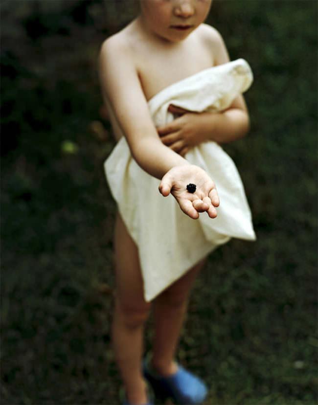 Kleines Kind hat eine einzelne Brombeere auf seiner ausgestreckten Hand und bedeckt seine Blöße mit einem Tuch.