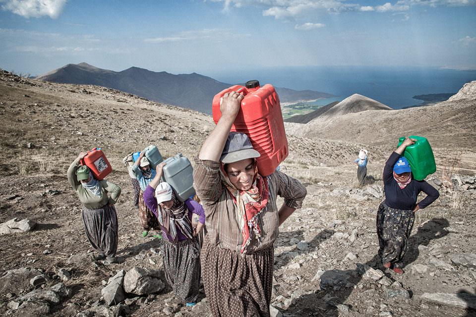 Frauen tragen Wasserkanister