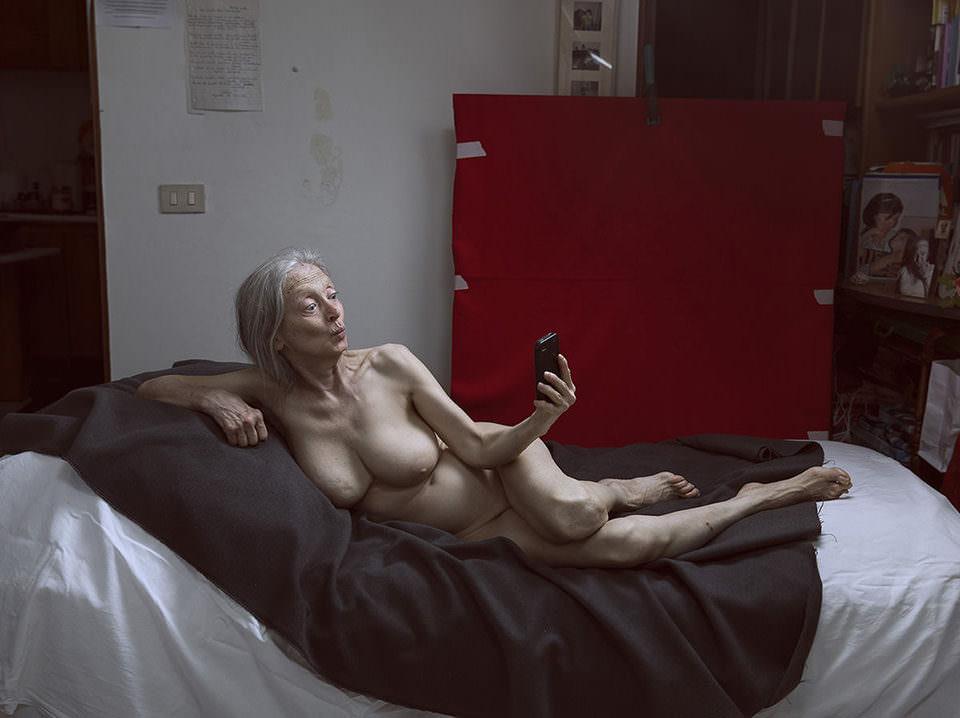 Eine nackte Frau fotografiert sich mit dem Handy
