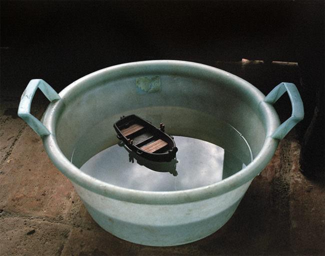 Playmobilboot in einer blauen Schale, schwimmend im Wasser.