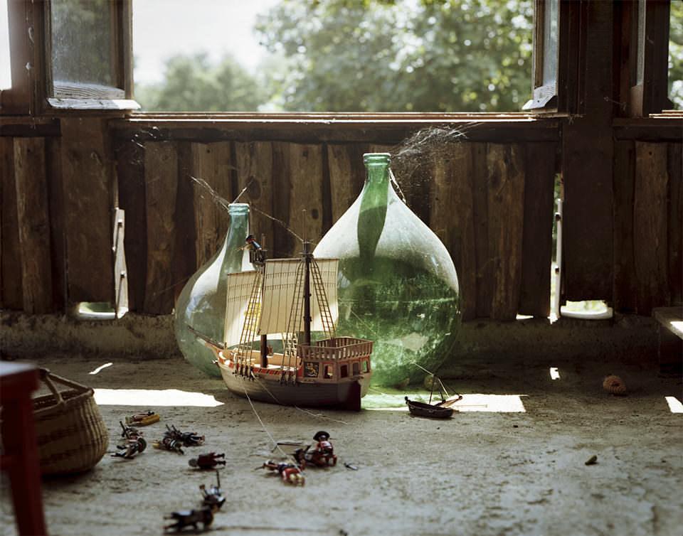 Playmobilschiff und Figuren vor eingestaubten, riesigen Weinflaschen.