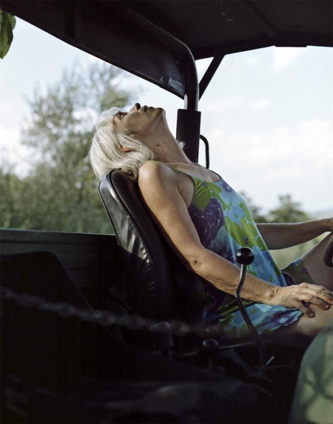 Ältere Dame mit zurückgelehntem Kopf auf einem Treckersitz