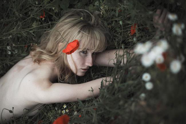 Eine Frau liegt in einer Blumenwiese