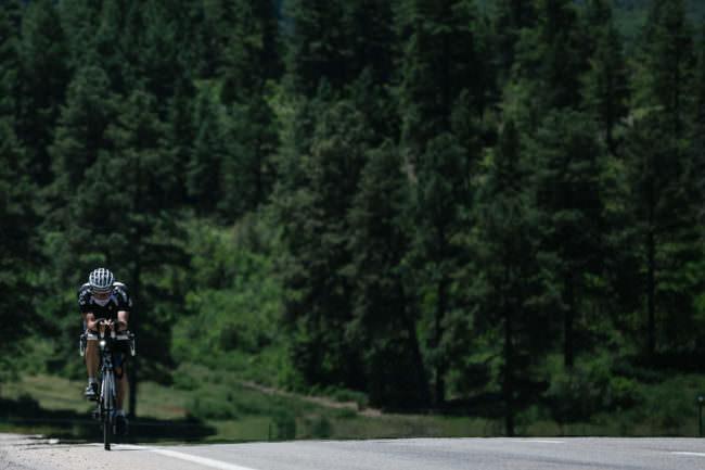 Ein Radfahrer auf einer Waldstraße
