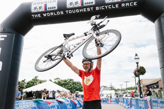 Ein Radfahrer hebt sein Rad am Ziel nach oben