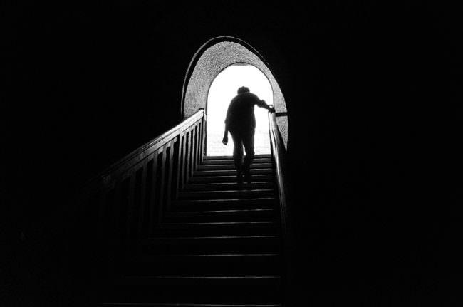 Eine Person geht durch einen Türbogen eine Treppe hinauf