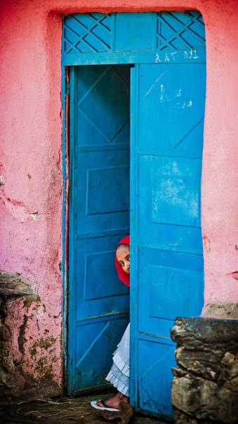Ein Gesicht schaut aus einer blauen Tür