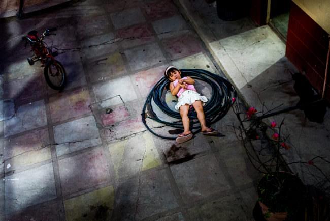 Ein Kind liegt in einem eingerolltem Schlauch
