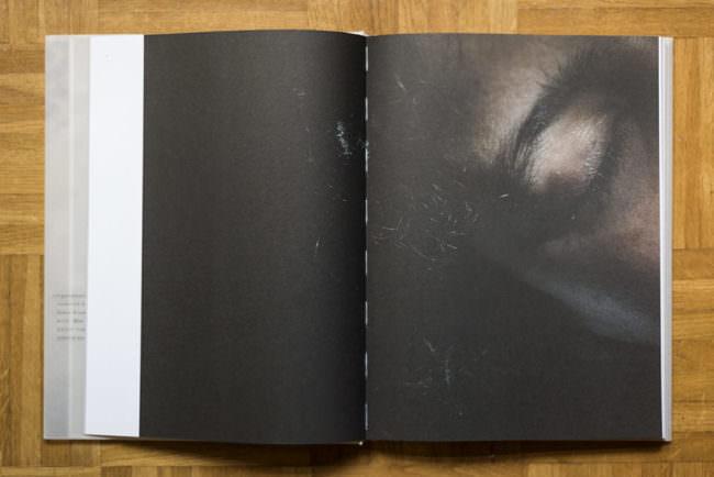 Aufgeschlagenes Buch mit fast formatfüllendem, dunklem Bild, auf dem schemenhaft ein geschlossenes Auge erkennbar ist.