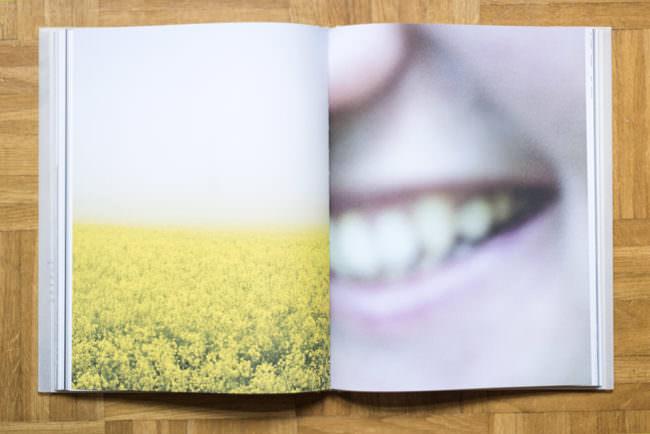 Aufgeschlagenes Buch mit zwei Fotografien. Linkerhand ein Rapsfeld und rechterhand Nahaufnahme eines lachenden Mundes.
