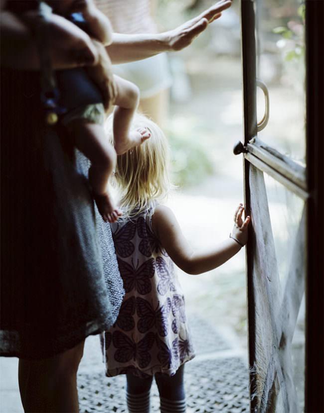 Kleines Kind in einer offenen Tür stehend, im Anschnitt erwachsene Person mit Baby auf dem Arm.