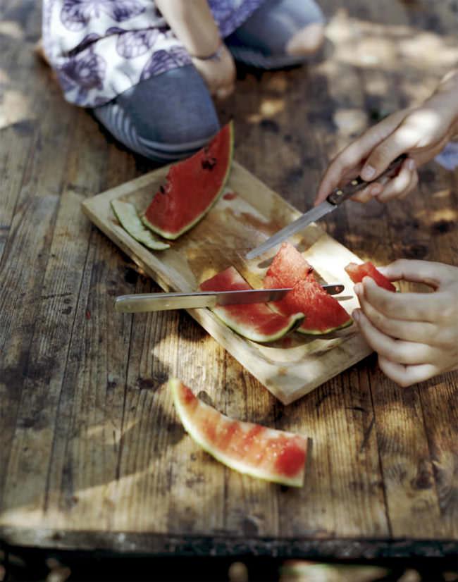 Aufgeschnittene Wassermelone, die grade verzehrt wird.