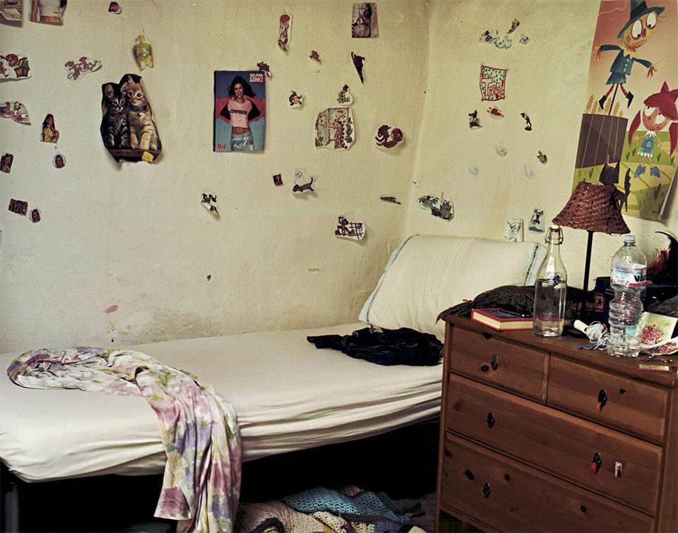 Zimmer mit ungemachtem Bett und vielen Zeitungsbildern an der Wand.