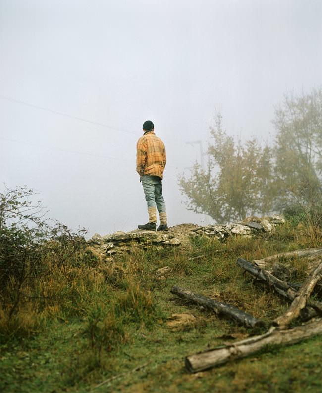 Mann in gelber Jacke draußen im Nebel von hinten.