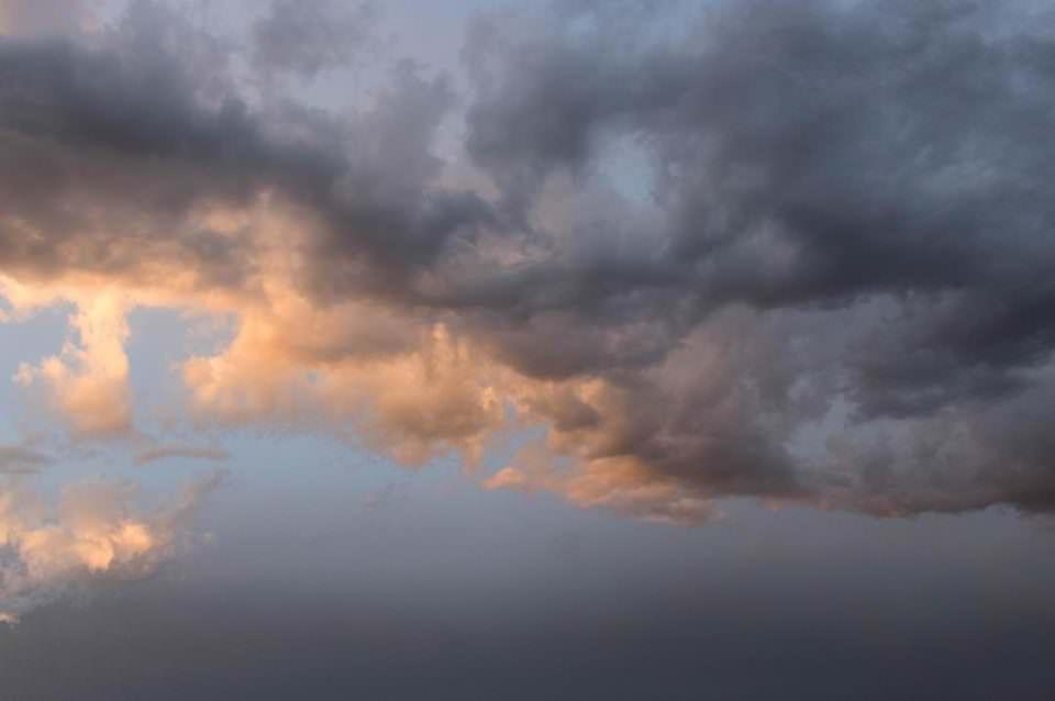 Ansicht eines halbdunklen Himmels mit von untergehender Sonne angestrahlten Wolken.