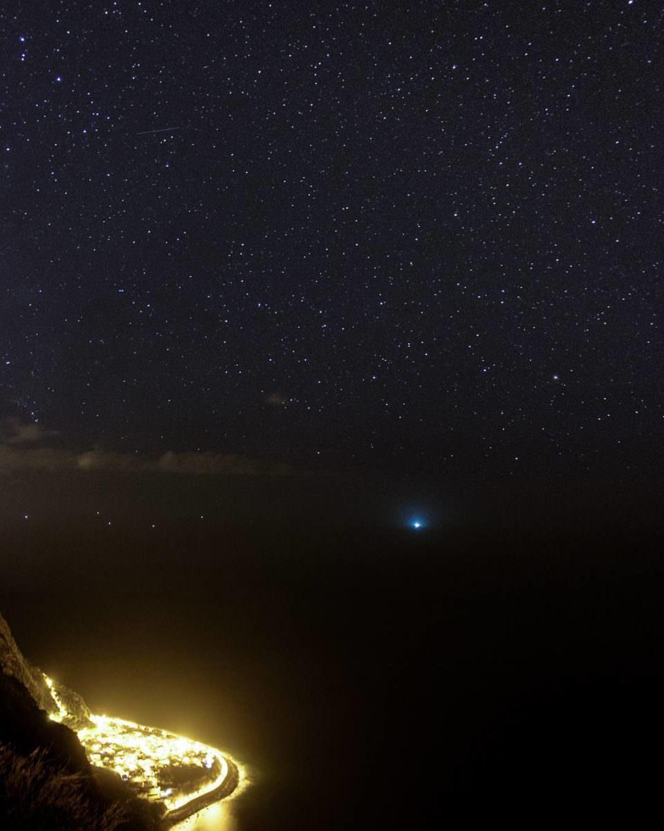 Nachthimmelansicht mit vielen Sternen. Links unten eine hell erleuchtete Stadt.