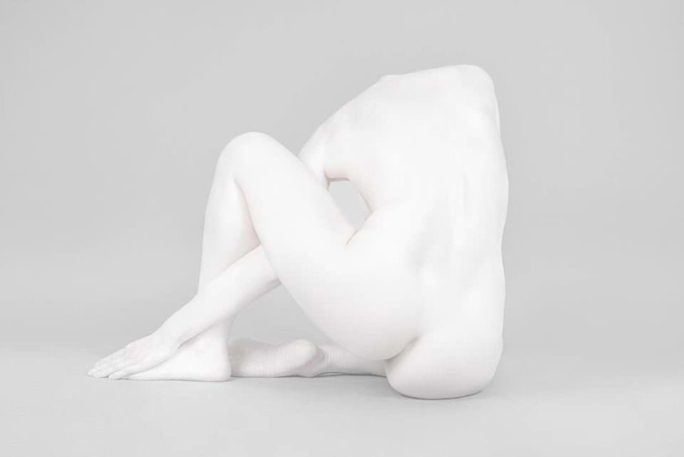 Frauenakt einer weiß angemalten Frau. Eine Rückansicht im Sitzen.