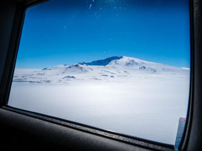 Ein verschneiter Berg aus einem Fenster heraus aufgenommen
