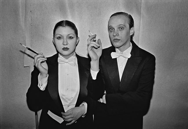 Zwei Personen im Anzug mit Zigarette