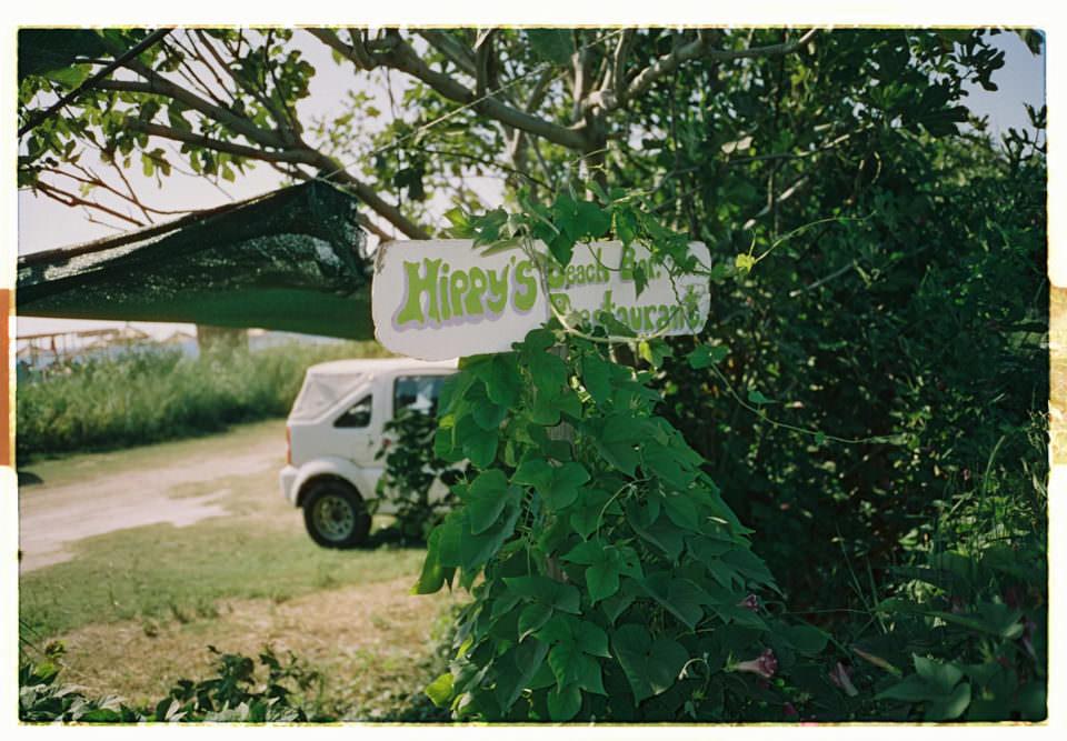Schild Hippy's Strandbar vor grünem Busch