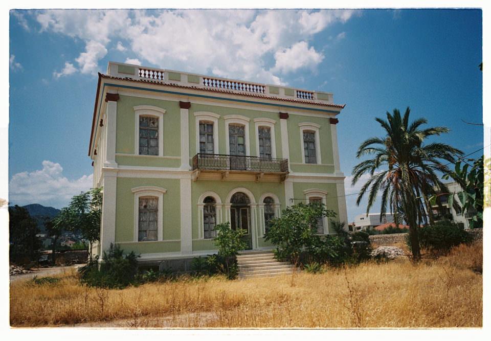 Grüne Villa vor blauem Himmel