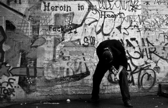 Ein Mann spritzt sich vor einer Wand mit Graffiti