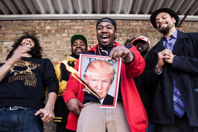 Männer verbrennen ein Time-Cover mit dem Bild von Trump