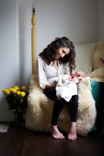 Frau mit dunklen Haaren sitzend mit Baby in der Hand welches sie anschaut.