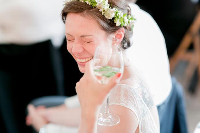 Eine Braut mit Sektglas lacht