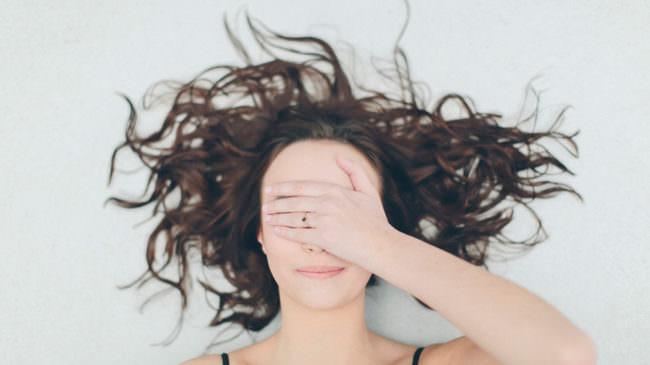 Eine Frau hält die Hand vor ihr Gesicht
