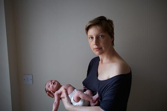 Junge Mutter mit Säugling im Arm.