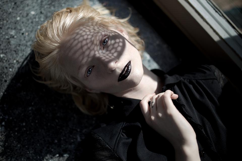 Eine Frau mit Schattenspiel im Gesicht und schwarzem Lippenstift