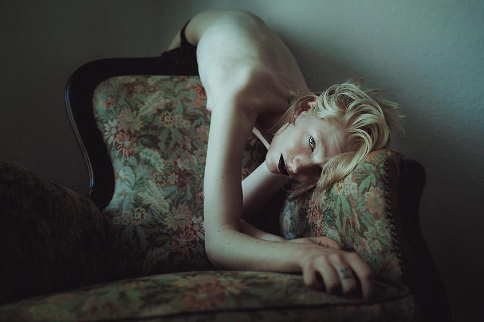 Eine Frau lehnt sich nackt über einen Stuhl