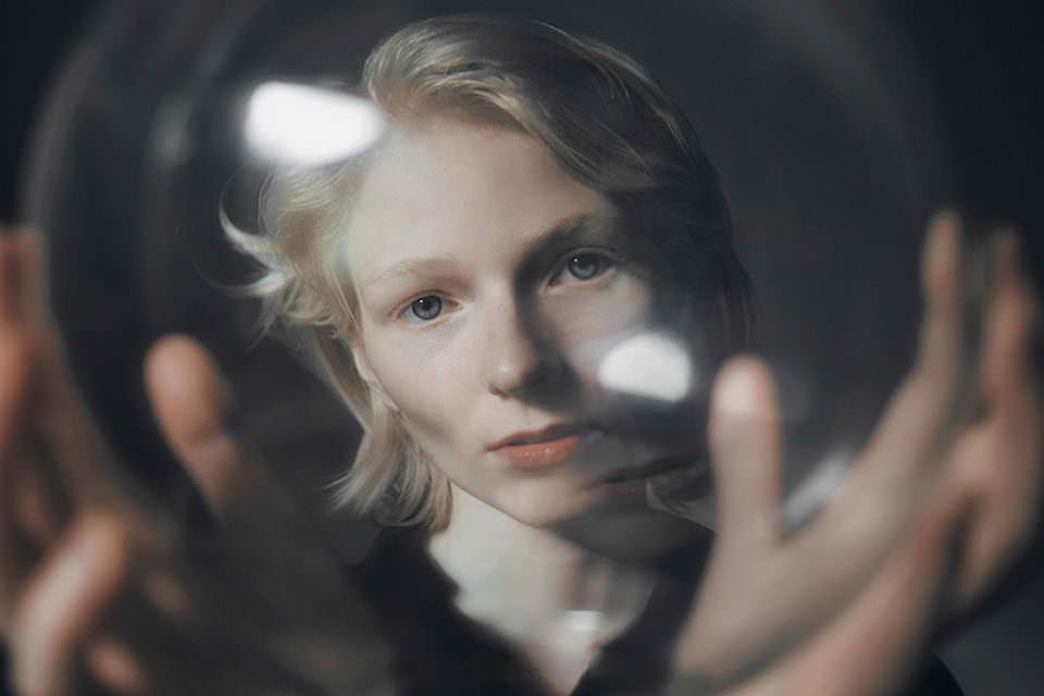 Eine Frau hält eine Glaskugel vor sich