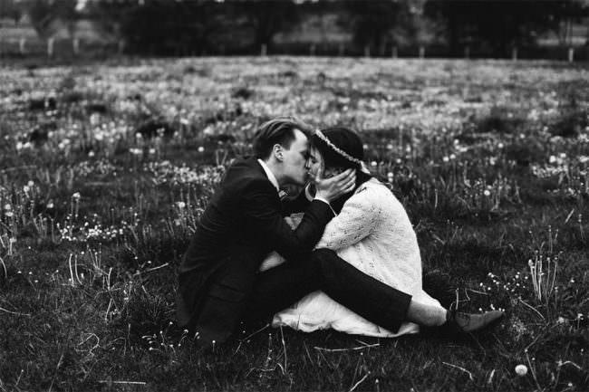 Ein Brautpaar küsst sich auf der Wiese sitzend