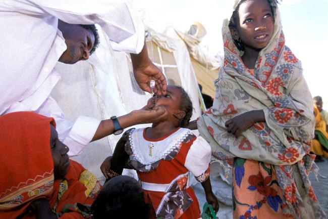 Arzt gibt Kind eine Schluckimpfung