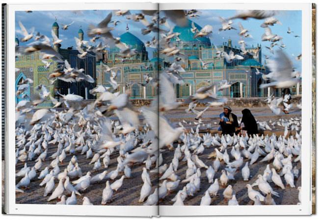 Offene Buchseite mit einem Bild von vielen Tauben auf einem Platz
