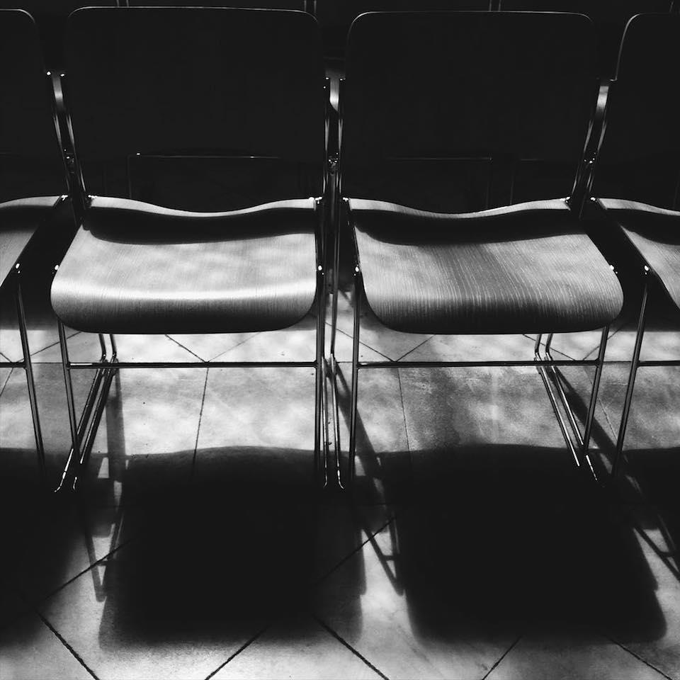 Nebeneinander stehende Stühle und deren Schatten.