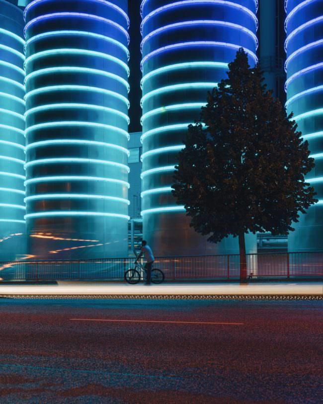 Nächtliche Szene mit blau beleuchteten Türmen.