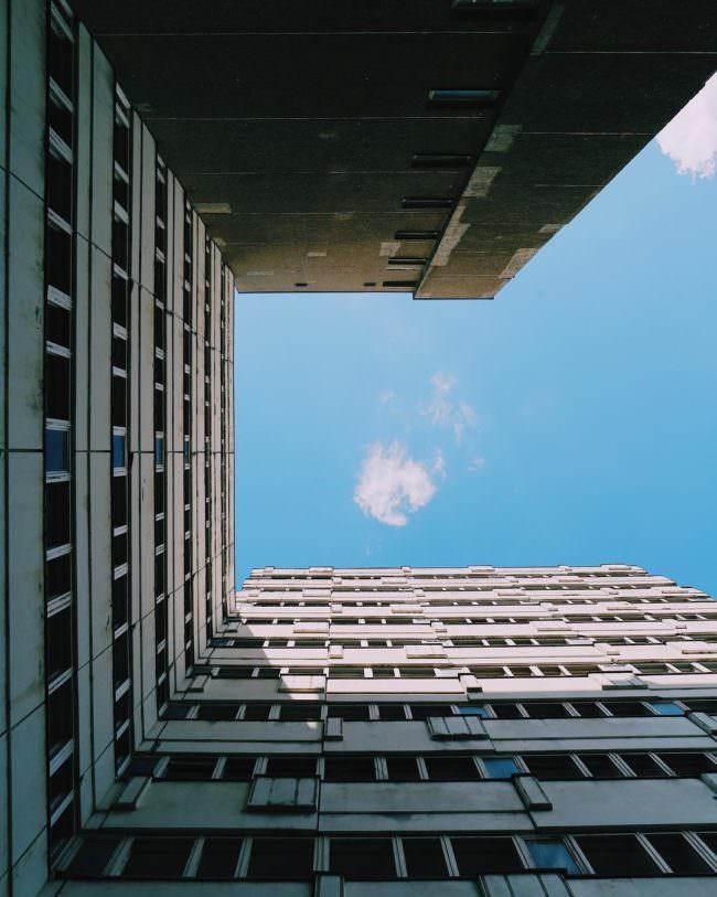 Blick nach oben durch eine Hochhausschlucht auf einen blauen Himmel.