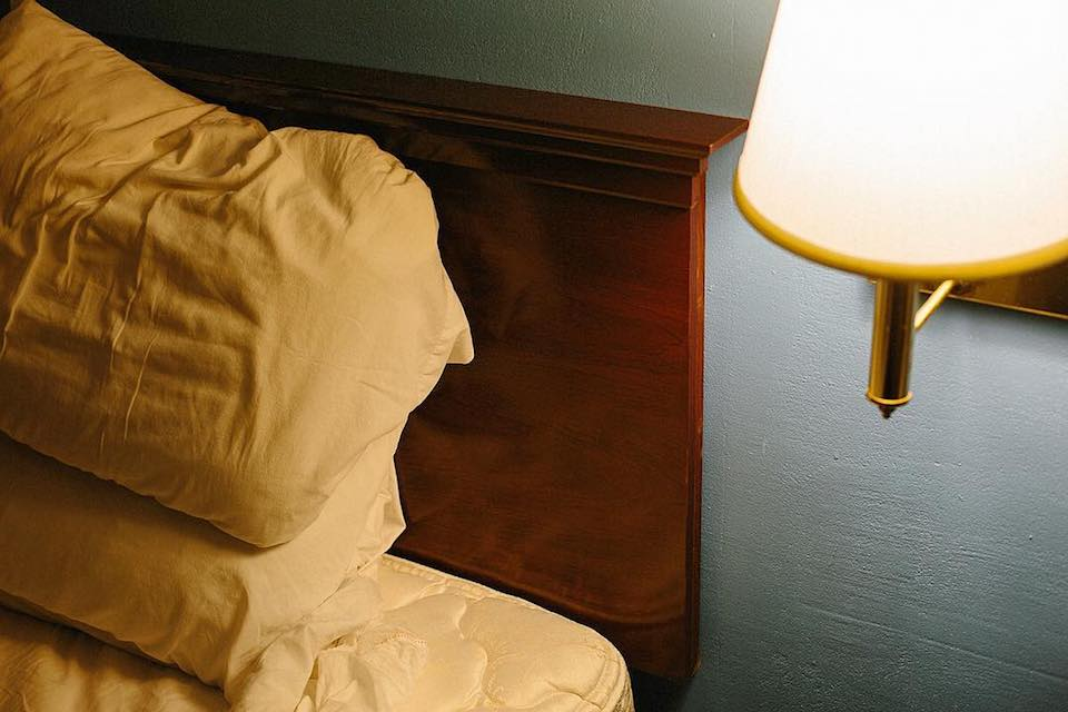 Ein Bett mit gelben Laken neben einer angeschalteten Nachttischlampe.