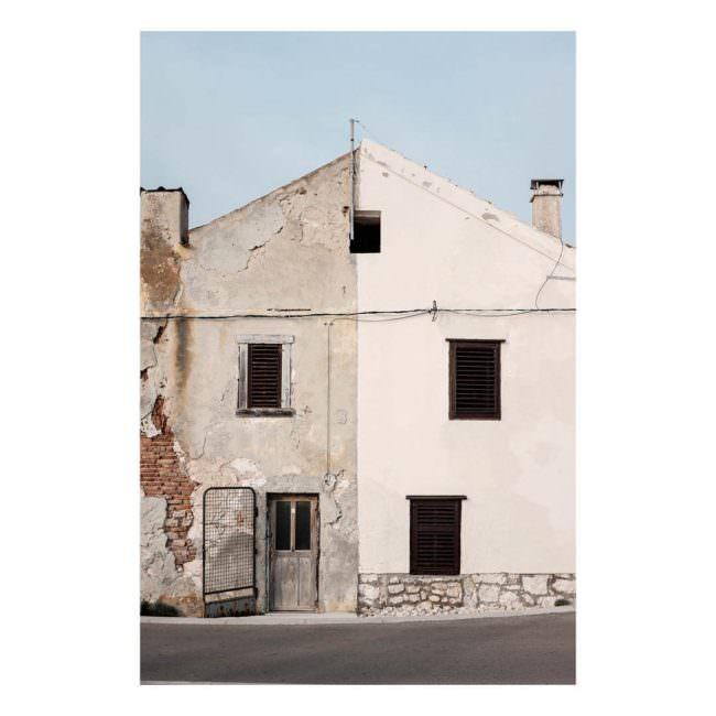 Ansicht eines Hauses von außen, bei dem eine Seite zerfällt und die andere frisch gestrichen ist.
