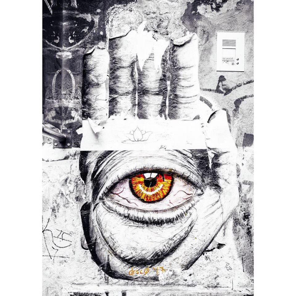 Beklebte Wand, die eine Hand zeigt in deren Handfläche ein oranges Auge zu sehen ist.