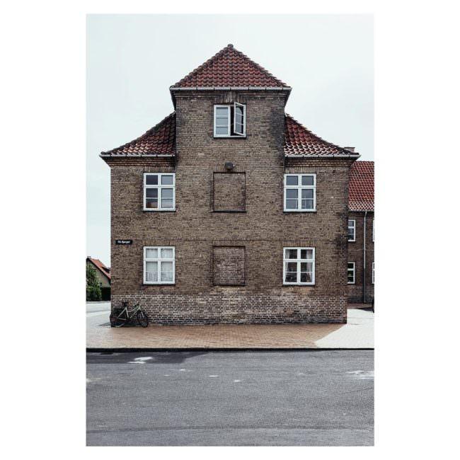 Ansicht eines Backsteinhauses mit sieben Fenstern, zwei davon sind zugemauert.