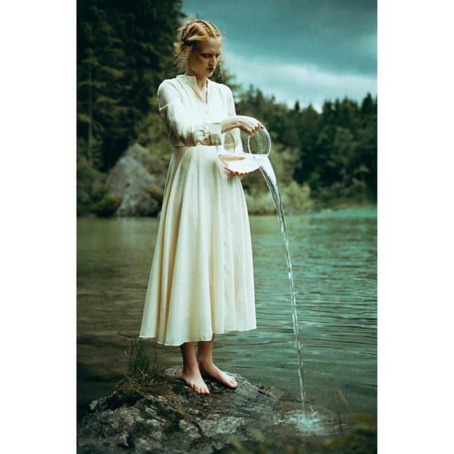 Junge Frau steht am Wasser in einem hellen Kleid und kippt aus einem Glasgefäß Wasser ins Wasser.