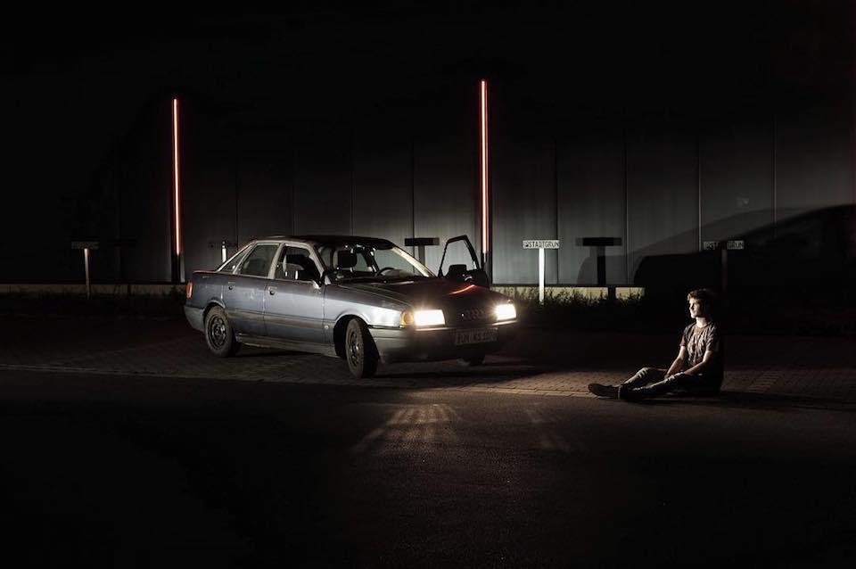 Ein mensch, der auf dem Boden sitzt und von den Lichtern eines Autos angestrahlt wird.